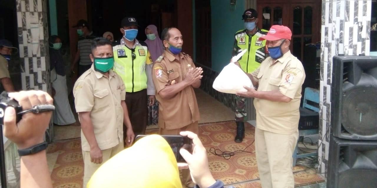 Kades Sumberagung, H Abdul Manan (Mbah Kung Haji Manan), ketika menyerahkan bantuan sembako secara simbolis kepada perangkatnya untuk dilanjutkan ke masing-masing rumah warga.